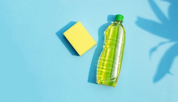 파란색 표면에 접시 세척 액체 병 주방 스폰지
