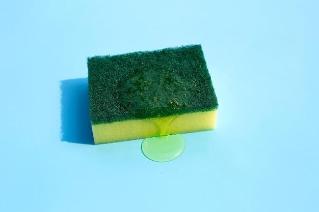 Kitchen sponge with dish washing liquid on blue background.