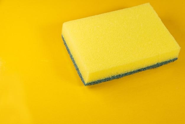 Kitchen sponge on the yellow background