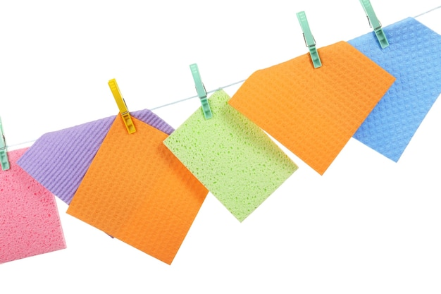 Kitchen sponges hanging on rope on white