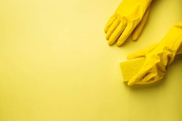 Kitchen sponges and rubber gloves on yellow background
