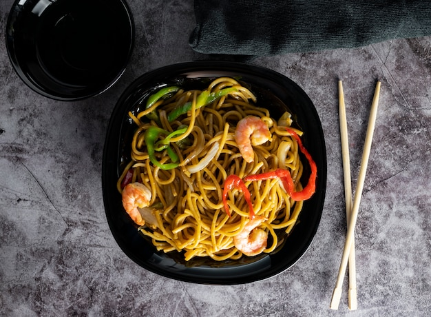 Kitchen stir udon noodles, vegetable, shrimp, with wooden chopsticks on gray textured space. flat floor. asian style dinner