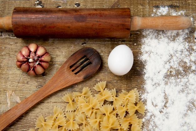 Кухонные принадлежности для приготовления пасты на деревенской доске Premium Фотографии
