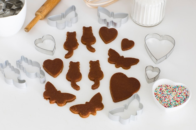 On the kitchen table are carved from ginger dough butterflies, cats, hearts, decor for decorating cookies.