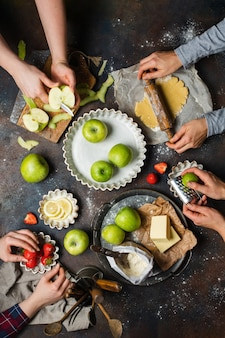 Kitchen table with apples, flour, butter, strawberries, and lemon