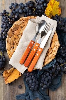 空の籐プレート、古い木製の背景に青いテーブルクロス、レシピやメニュー用のスペースが付いたキッチンテーブル。ヴィンテージスタイル。上面図。モックアップ。