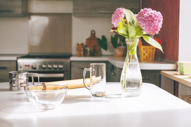 Кухонный стол со скалкой и прозрачной стеклянной чашей, чашкой и вазой для цветов