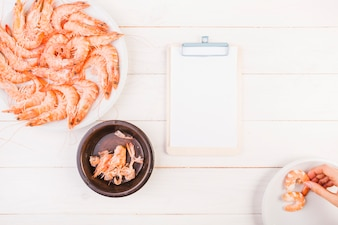 Kitchen table with shrimps and clipboard with hand holding piece