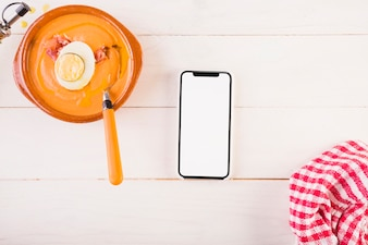 Kitchen table with soup plate and smartphone