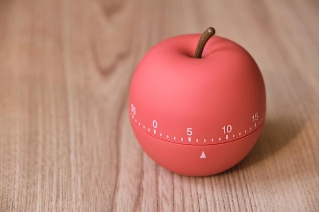 탁자 위의 햇볕이 잘 드는 주방에 사과 모양의 주방 타이머, 분으로 설정된 카운터