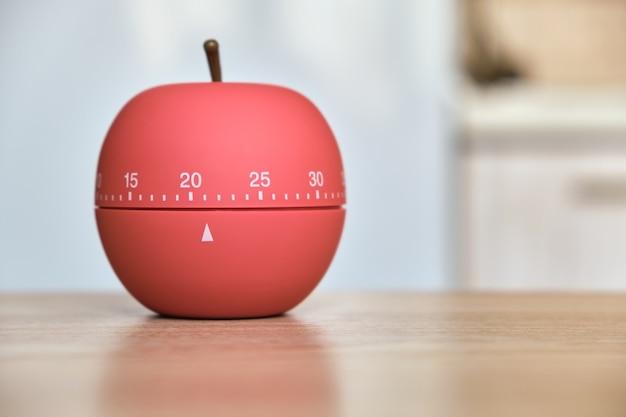 테이블 위의 햇볕이 잘 드는 주방에 사과 모양의 주방 타이머, 22 분 카운트 다운