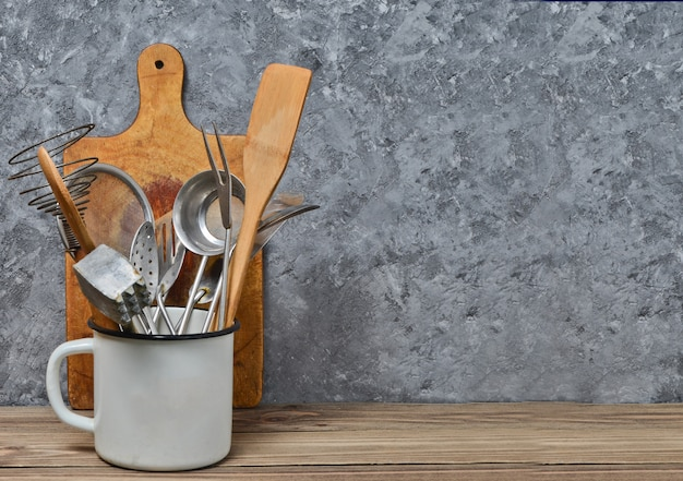 Kitchen tools for cooking on a wooden table on the background of a concrete wall.copy space. spoons, forks, wooden spatula.