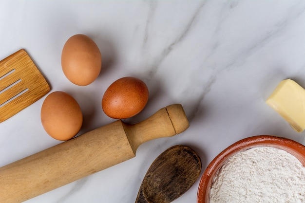 Kitchen tools, eggs, flour and butter.