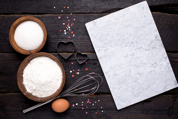 Kitchen tools, flour and sugar on wood