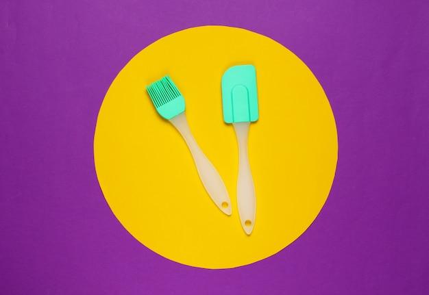 真ん中に黄色の円が付いた紫色のキッチンツール