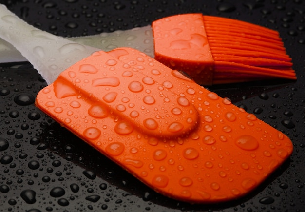 Kitchen tools in water drops on black background. silicone spatula, brush close up