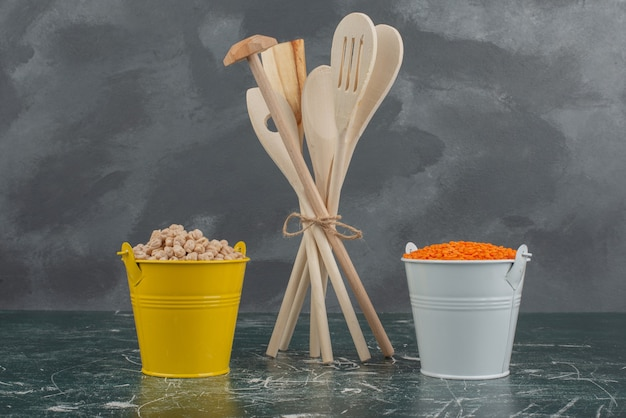 Kitchen tools with two colorful buckets of nuts on marble surface