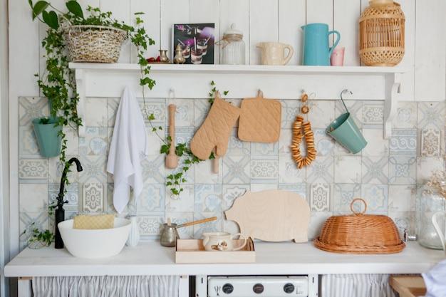 Кухонное полотенце и перчатки на рабочей поверхности в современной кухне, кухонные принадлежности, висящие на рейлинге на белой стене