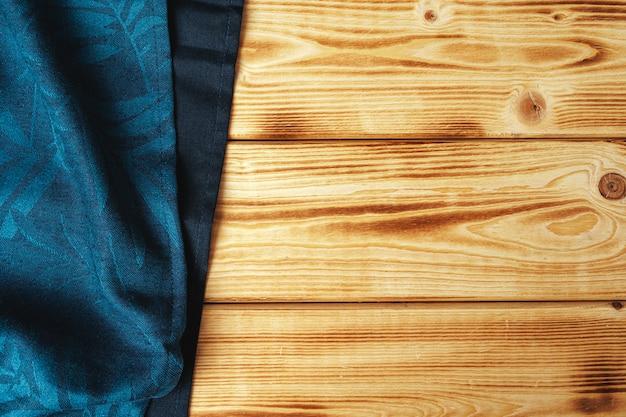 Кухонное полотенце или салфетка над деревянным столом.