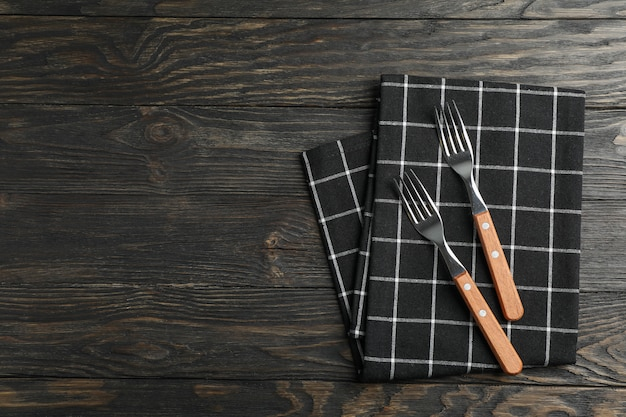 Kitchen towel with cutlery on wooden background, top view