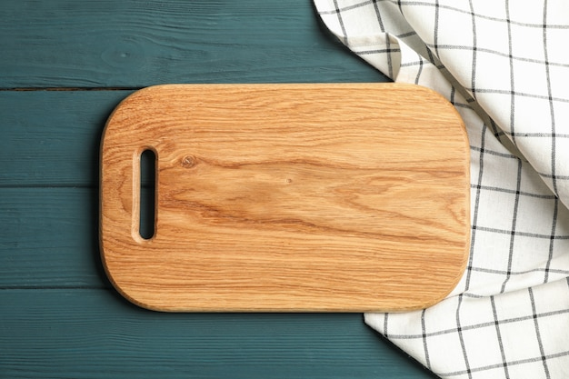 Kitchen towel with cutting board on wooden background, top view
