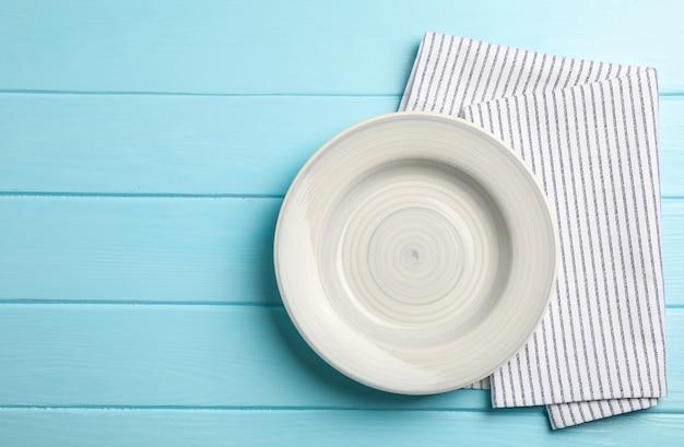Кухонное полотенце с тарелкой на деревянном фоне, вид сверху