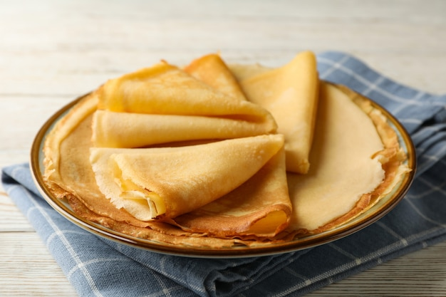 Kitchen towel with plate of thin pancakes on wooden background