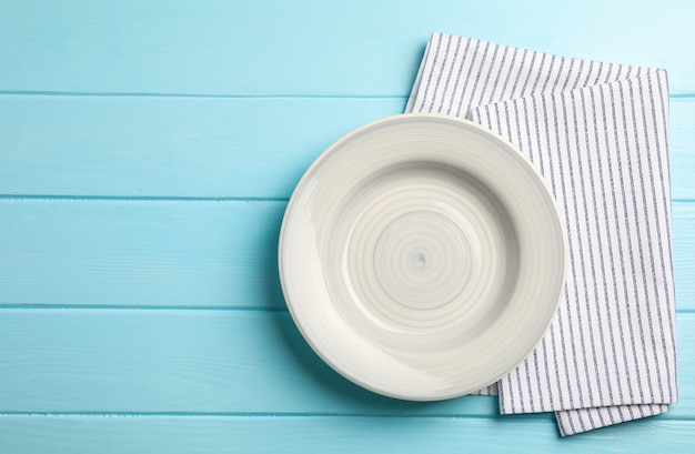Kitchen towel with plate on wooden background, top view