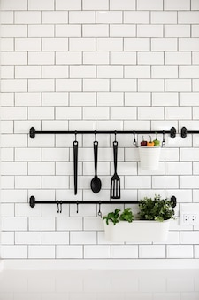 Kitchen utensil hanger on white brick wall