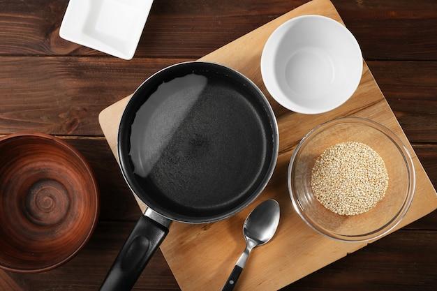 木製のテーブルのボウルに台所用品とキノアの種