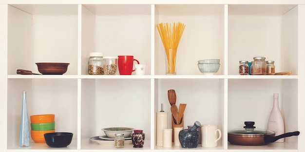 Кухонная утварь и посуда на белых полках. хорошо организованная концепция кухни. современный интерьер. откройте шкаф с чистой посудой. открытые полки на кухне.