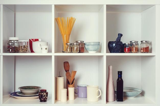 흰색 선반에 주방 용품과 식기. 잘 정리된 주방 컨셉입니다. 현대적인 인테리어입니다. 깨끗한 접시가 있는 오픈 찬장