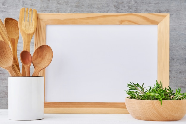 Kitchen utensils background with empty white paper and wooden cutlery in cup
