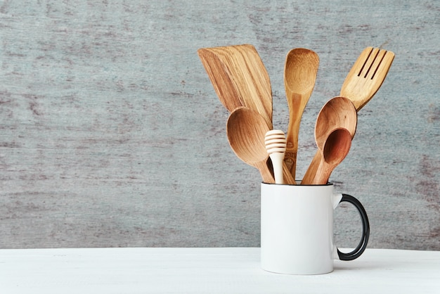 Kitchen utensils in ceramic cup on a gray background, copy space