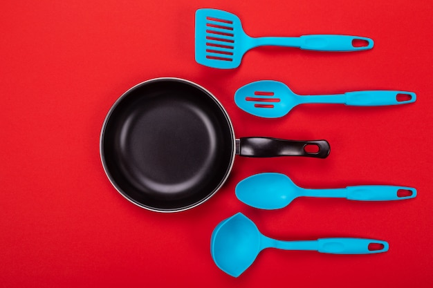 Kitchen utensils for cooking in kitchen isolated with copyspace on red background