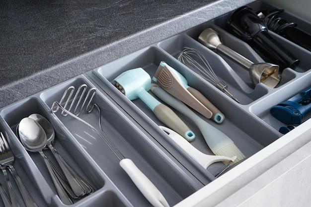 Kitchen utensils in drawer, above view.