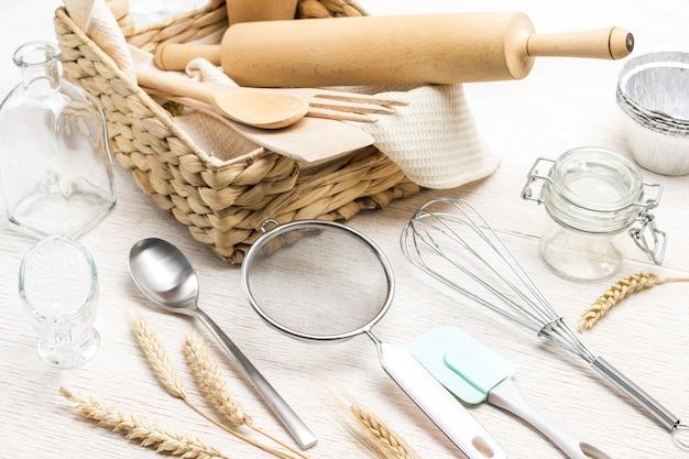 Кухонная утварь для замеса теста. колоски пшеницы. плетеная шкатулка. белый фон. вид сверху