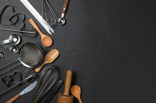 Кухонная утварь для выпечки на черном столе и копией пространства, подготовка к созданию торта и концепции пекарни