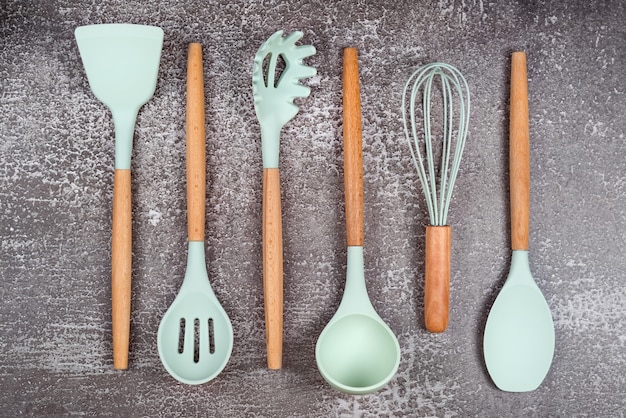 Kitchen utensils, home kitchen tools, mint rubber accessories on dark background. restaurant, cooking, culinary, kitchen theme. silicone spatulas and brushes, free space for text.