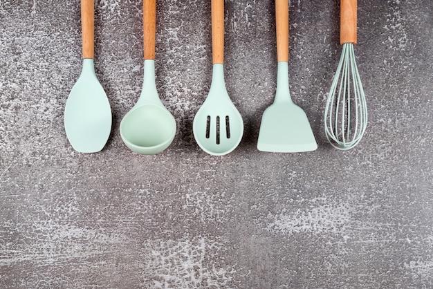 台所用品、家庭用キッチンツール、暗い背景のミントラバーアクセサリー。レストラン、料理、料理、キッチンのテーマ。シリコンヘラとブラシ、テキスト用の空きスペース。