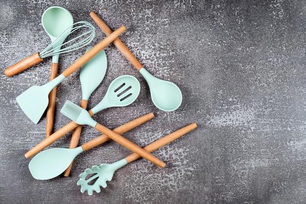 주방 용품, 가정용 주방 도구, 어두운 배경에 민트 고무 액세서리. 레스토랑, 요리, 요리, 주방 테마. 실리콘 주걱 및 브러시, 텍스트를위한 여유 공간.