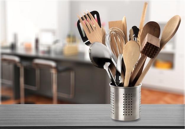 Кухонная утварь в оловянном каноне размытым кухонным фоном
