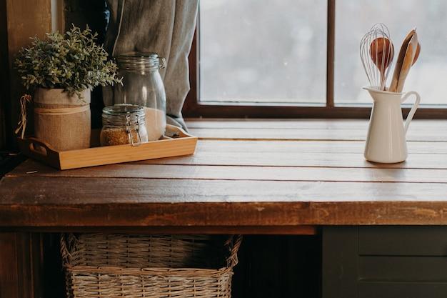 窓の近くの木製のテーブルの上の白い容器の台所用品。家庭の台所の装飾。台所用品。調理する時間です。部屋のカトラリー。