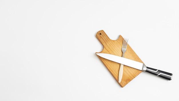 台所用品:金属刃のナイフ、まな板の上の黒いハンドルとフォーク