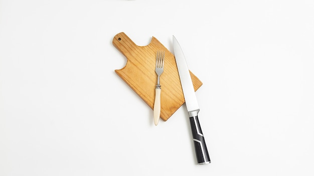 Kitchen utensils: knife with metal blade, black handle and fork on cutting board