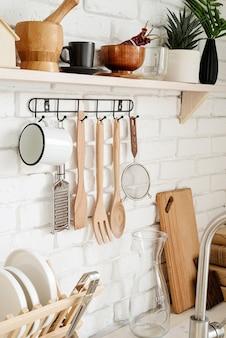 Кухонная утварь на черной металлической вешалке в деревенской кухне