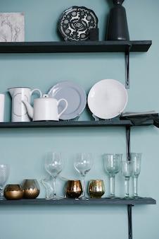Кухонная утварь на полках: стеклянные стаканы, золотые стаканы, тарелки, чайники на кухне.