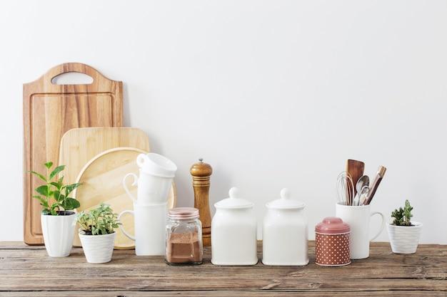 Кухонная утварь на деревянном столе в белой кухне