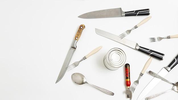 Kitchen utensils: opener, forks, sharp metal knives, teaspoons, tin isolated