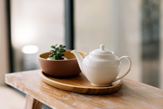 Кухонная утварь, такая как чайник, кофейник, на деревянном подносе. ранний завтрак. мягкий выборочный фокус.